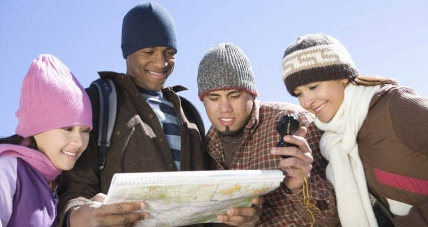 A group of friends with a map preparing to go hiking in the Smoky Mountains in the winter.