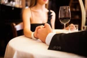A couple holding hands at a romantic dinner in a restaurant.