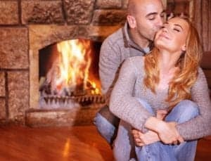 A happy couple embracing in front of the fireplace in their cabin.