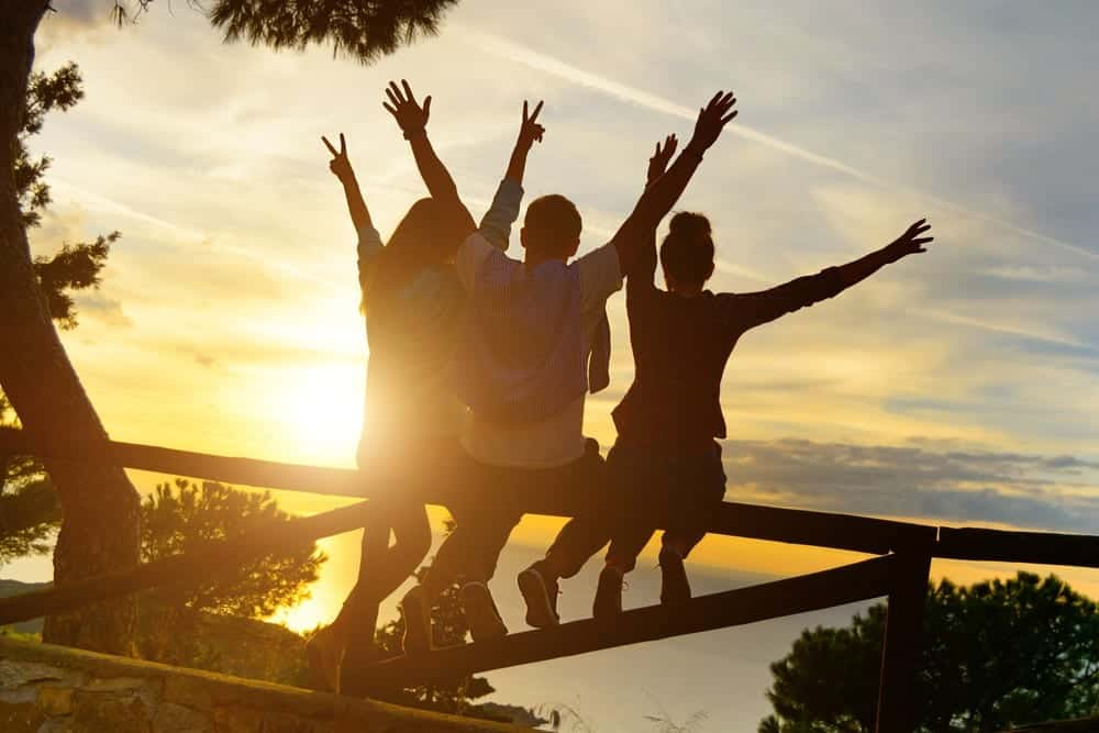 Rear view of three best friend travelers putting their hands up at sunset.